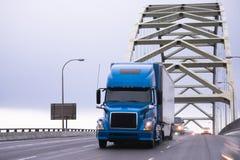 Halv lastbil för blå stor rigg som transporterar den halva släpet på välvda Frem Arkivbilder