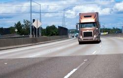 Halv lastbil för modern guld- stor rigg med torra skåpbil släp som är rörande på wi Arkivfoto