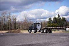 Halv lastbil för stilfull svart stor rigg med halv släprunn för plan säng Royaltyfria Bilder