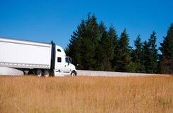 Halv lastbil för stor rigg med halv släpflyttning vid körbanan med gree Arkivbilder