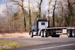 Halv lastbil för stor riggsvart med halv släpspring för plan säng på w Arkivbilder