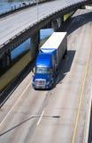 Halv lastbil för stora riggblått som transporterar den dolda halva släpet på tur Royaltyfria Bilder