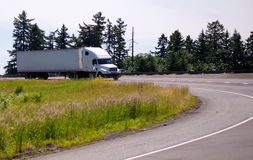 Halv lastbil för vit stor rigg med den långa släpet som är roterande på huvudvägföre detta Fotografering för Bildbyråer