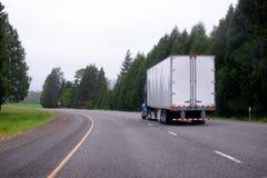 Halv lastbil med den halva lastbilen för torr skåpbil som är rörande på scenisk curvy highwa arkivfoto