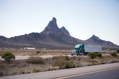 Halv lastbil och släp på vägen av Arizona med berget Royaltyfri Bild