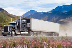 Halv lastbil på den dammiga vägen i berglandskap Royaltyfri Bild