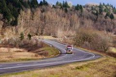 Halv lastbilrigg på den slingriga vägen med vinterträd Arkivfoto