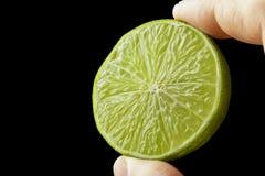 Halv limefrukt i handen av en man arkivfoto