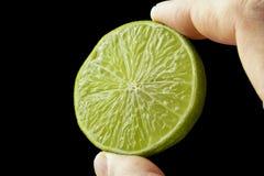 Halv limefrukt i handen av en man royaltyfria foton