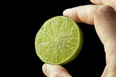 Halv limefrukt i handen av en man arkivbild