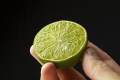 Halv limefrukt i handen av en man royaltyfri bild
