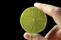 Halv limefrukt i handen av en man arkivfoton