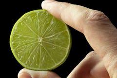 Halv limefrukt i handen av en man royaltyfri fotografi