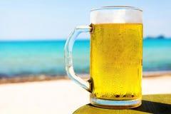 Halv liter av kallt öl överst av strandtabellen royaltyfri foto
