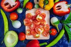 Halv snitttomatbakgrund och sunda grönsaker fotografering för bildbyråer