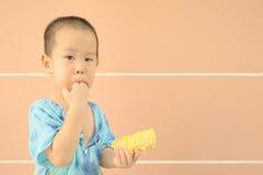 Halv stående av den Asien pojken i äten gul havre för litet barnålder innehav Arkivbild