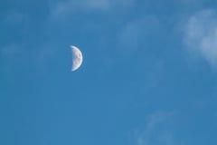 Halv vaxande måne i blå himmel Arkivfoto