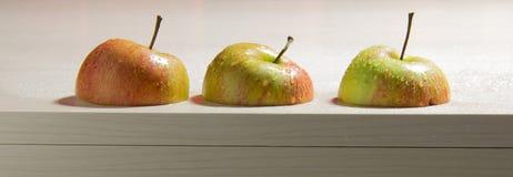 Halva äpplen på trä Arkivbild
