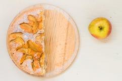 Halva av äppelpajen och ett äpple Arkivbilder