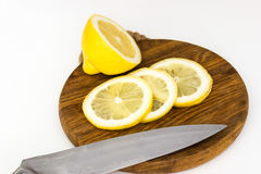 Halva av citron och skivor på skärbräda med kniven Fotografering för Bildbyråer