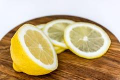 Halva av citron och tre skivor på träskärbräda Fotografering för Bildbyråer