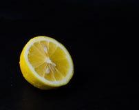 Halva av den saftiga citronen i vattensmå droppar arkivfoton