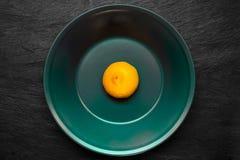 Halva av för citron plattan för grön färg in djupt - som förlade på svart stenyttersida Royaltyfri Fotografi