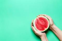 Halva av söta Mini Watermelon i kvinnliga händer med grönt kopieringsutrymme Royaltyfri Foto