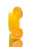 Halva en apelsin och ett exponeringsglas av orange fruktsaft på vitbakgrund Fotografering för Bildbyråer
