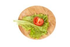 Halva av tomat och grönsallat på en bästa sikt för skärbräda Fotografering för Bildbyråer