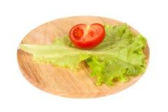 Halva av tomat och grönsallat på en skärbräda Arkivfoto