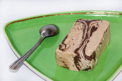 Halva with chocolate on the green plate Royalty Free Stock Image