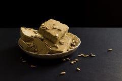 Halva del girasole con i semi sul piatto, su fondo nero Immagini Stock