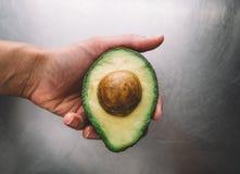 Halva en avokado i en hand på bakgrunden av en horisontalbästa sikt för ståltabell, ny sund matfrukost på kök, gräsplan royaltyfri bild