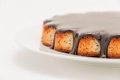 Halva en kaka av mangaen med choklad som täckas i en platta på en vit bakgrund isolerat arkivfoto