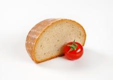 Halva en släntra av kontinentalt bröd och tomaten arkivfoton