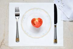 Halva en tomat i form av en hjärta på en målad platta Begrepp av vegetarisk mat Begränsningar på mat Liten del av matnolla arkivbilder