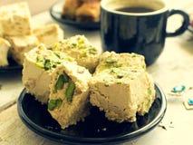 Halva filiżanka kawy i pistacja Zdjęcia Stock