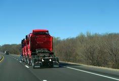 Halva halva lastbilar för traktorlastbilstransport som tre är röda, på huvudvägen Arkivfoto