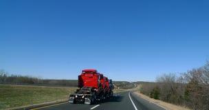 Halva lastbilar för halv traktorlastbilstransport som är röda, på huvudvägen Royaltyfria Foton