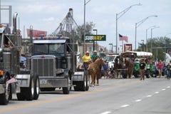 Halva lastbilar, hästar och flaggor i en ståta i lilla staden Amerika Royaltyfri Foto