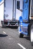 Halva lastbilar med släp som går i eskortfartyg på vägen arkivbilder
