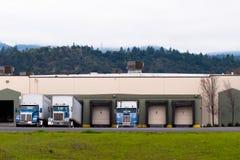 Halva lastbilar slösar släp som laddar lasta av last i lager b Royaltyfria Bilder