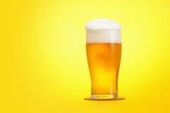 Halva liter av öl på gul bakgrund Arkivbild