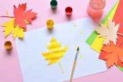 Halva-målad lönnlöv, målarfärg och borste Oavslutat arbete quitter Passerande av svårigheter hösten tappar melankoliskt förser me arkivbild