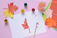 Halva-målad lönnlöv, målarfärg och borste Oavslutat arbete quitter Passerande av svårigheter hösten tappar melankoliskt förser me fotografering för bildbyråer