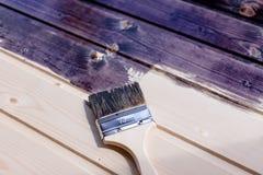 Halva målad träyttersida Djup svart färg Lacka naturligt trä med målarfärgborsten målarfärgträyttersida Reparation och royaltyfria foton