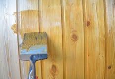 Halva målad träyttersida Gul färg Lacka naturligt trä med målarfärgborsten royaltyfri fotografi