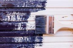 Halva målad träyttersida svart färg Lacka naturligt trä med målarfärgborsten Måla den naturliga träväggen med borsten arkivbilder