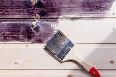 Halva målad träyttersida svart färg Lacka naturligt trä med målarfärgborsten Måla den naturliga träväggen med borsten royaltyfri fotografi